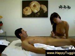 Bigbreasted Asian masseuse wanks a cock