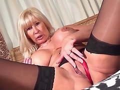 MILF gets her dildo wet then crams it into her tight, wet pussy