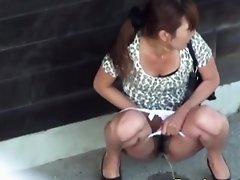 Leggy asian babe urinates outdoors